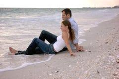 Schöne Paare am Strand, der im Wasser gekleidet sitzt Lizenzfreie Stockfotografie