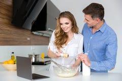 Schöne Paare unter Verwendung des Laptops und zusammen kochen Stockfotos