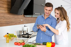 Schöne Paare unter Verwendung des Smartphone und des Kochens Stockfotos