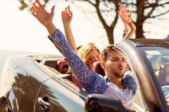 Schöne Parteifreundmädchen, die in ein Auto auf dem Strand glücklich tanzen Stockfotografie