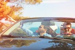 Schöne Parteifreundmädchen, die in ein Auto auf dem Strand glücklich tanzen Lizenzfreie Stockfotografie