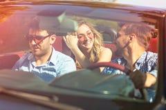 Schöne Parteifreundmädchen, die in ein Auto auf dem Strand glücklich tanzen Lizenzfreie Stockbilder