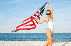 Schöne patriotische Frau, die eine amerikanische Flagge auf dem Strand hält USA-Unabhängigkeitstag, am 4. Juli stockbilder