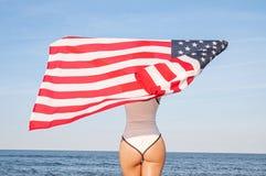 Schöne patriotische Frau, die eine amerikanische Flagge auf dem Strand hält USA-Unabhängigkeitstag, am 4. Juli Getrennt auf Schwa stockfoto