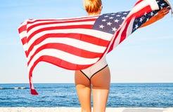 Schöne patriotische Frau, die eine amerikanische Flagge auf dem Strand hält USA-Unabhängigkeitstag, am 4. Juli Getrennt auf Schwa lizenzfreie stockfotografie
