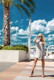 Schöne phänomenale erstaunliche elegante sexy blonde vorbildliche Luxusfrau, die ein Kleid und hohe Absätze und Sonnenbrille träg Stockfotos