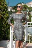 Schöne phänomenale erstaunliche elegante sexy blonde vorbildliche Luxusfrau, die einen eleganten Anzug und hohe Absätze und Sonne Stockfoto