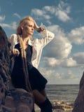 Schöne Piratenfrau, die auf dem Strand in den Stiefeln steht Lizenzfreies Stockbild