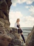 Schöne Piratenfrau, die auf dem Strand in den Stiefeln steht Stockfotografie