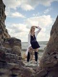 Schöne Piratenfrau, die auf dem Strand in den Stiefeln steht Stockfoto