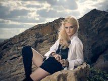 Schöne Piratenfrau, die auf dem Strand sitzt Lizenzfreies Stockfoto