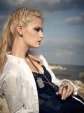 Schöne Piratenfrau, die auf dem Strand sitzt Stockfotos