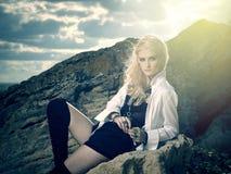 Schöne Piratenfrau, die auf dem Strand sitzt Lizenzfreie Stockfotografie