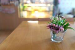 Schöne Plastikblumen auf Glasvase auf Holztisch im Bäcker lizenzfreie stockbilder