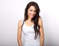 Schöne positive Frau in toothy SMI des weißen Hemdes und des langen Haares lizenzfreie stockbilder