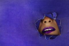 Schöne pralle, helle purpurrote Lippen fallen in den Schlitz des farbigen Papiers Kosmetik, Kosmetik, Schönheitssalon, Maskenbild lizenzfreies stockfoto