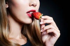 Schöne Probierenerdbeere der jungen Frau Stockfoto