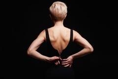 Schöne Rückseite der jungen Frau in einem schwarzen sexy Kleid Stockfoto