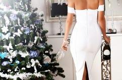 Schöne Rückseite der jungen Frau in einem weißen sexy Kleid mit champag Lizenzfreie Stockfotos