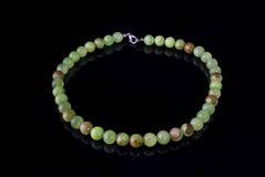 Schöne, raffinierte Halskette des grünen Onyxes bördelt auf einem schwarzen Hintergrund Lizenzfreie Stockbilder