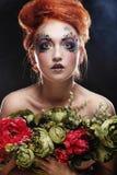 Schöne redhair Frau, die Blumen hält stockfoto