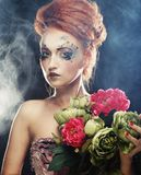 Schöne redhair Frau, die Blumen hält lizenzfreie stockfotos