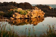 Schöne Reflexion eines Felsens in einem kleinen Teich durch das Meer Lizenzfreies Stockfoto