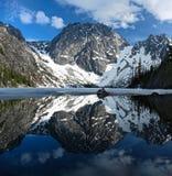Schöne Reflexionen von den felsigen Bergen bedeckt mit Schnee im ruhigen klaren Wasser von alpinem See Stockfotos