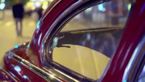 Schöne Reflexionen von Lampen im Retro- Glas des Autos Leuteweg die Straße an einem Autohintergrund Nachtlampen werden reflektier stock video