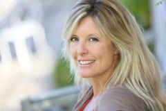Schöne reife blonde Frau, die draußen genießt lizenzfreie stockfotos