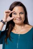Schöne reife Frau, die ihr Auge mit ihrer Hand öffnet Stockfotos