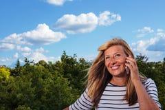 Schöne reife Frau, die am Telefon spricht Stockbild