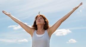 Schöne reife Frau, die weit ihre Arme zum Himmel öffnet Lizenzfreies Stockfoto