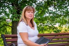 Schöne reife Frau h mit einem Laptop Lizenzfreies Stockbild
