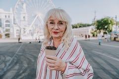 Schöne reife Frau trinkt Kaffee auf Quadrat lizenzfreies stockfoto