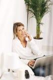 Schöne reife Geschäftsfrau, die mit Laptop im Bett arbeitet. Stockfotos