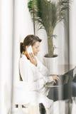 Schöne reife Geschäftsfrau, die mit Laptop im Bett arbeitet. Stockfotografie