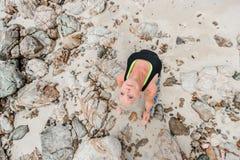 Schöne reife Greisin, die Yoga auf einem Wüste tropischen beac tut stockfotografie