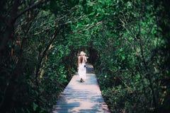 Schöne Reisendfrau im weißen Kleid, im Turnschuh und im Strohhut lizenzfreies stockbild