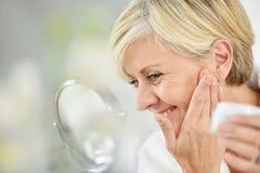 Schöne reizend ältere Frau, die Creme auf ihr Gesicht setzt Stockfoto