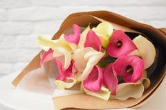 Schöne reizende Callas im stilvollen Kraftpapier auf weißer Tabelle lizenzfreie stockbilder
