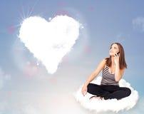 Schöne reizende Frau, die auf Wolke mit Herzen sitzt Lizenzfreies Stockfoto