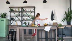 Schöne reizende Frau, die lustigen Bewegungs-, Warten Ehemann tanzt und oben Hände, moderne Küche im Hintergrund anhebt stock video