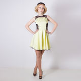 Schöne reizende leichte elegante junge blonde Frau in einem gelben Sommerkleid mit pricheskoyi Blumenkranz in ihrem Haar Stockfoto