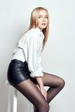 Schöne reizvolle blonde Frau Mädchen mit dem perfekten Körper, der auf Schemel sitzt Schönes langes Haar und Beine, glatte sauber Lizenzfreie Stockbilder