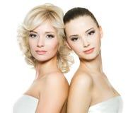 Schöne reizvolle junge erwachsene Frauen, die auf Weiß aufwerfen Stockfotos