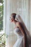 Schöne romantische blonde Braut, die heraus Fenster in den weißen dres schaut Lizenzfreie Stockfotografie
