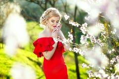 Schöne romantische junge Frau in einem Kranz von den Blumen, die auf einem Hintergrund von Blumen aufwerfen Inspiration des Frühl Lizenzfreie Stockbilder