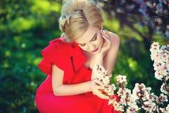 Schöne romantische junge Frau in einem Kranz von den Blumen, die auf einem Hintergrund von Rosen aufwerfen Inspiration des Frühli Stockbild