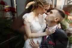 Schöne romantische Jungvermähltenpaare, die nahe Blumenblumensträußen umarmen Stockbilder